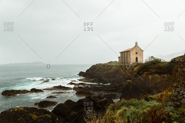 Ocean with big stones near hill with antique building and mountain far away under white sky
