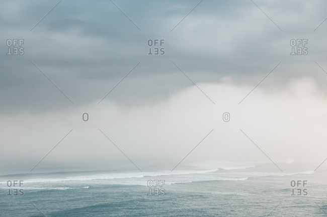 Picturesque view of ocean partially covered with mist passing near hillside under cloudy sky in afternoon in Mundaka, Basque Country in spain