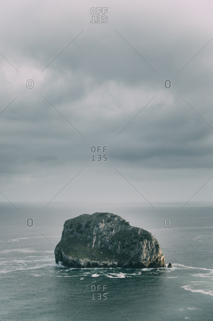 Picturesque view of rocky cliff with uneven surface washed by ocean waves in cloudy weather
