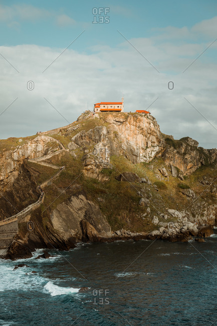 Picturesque view of rock with natural arches and house on top surrounded by sea in afternoon on cloudy day