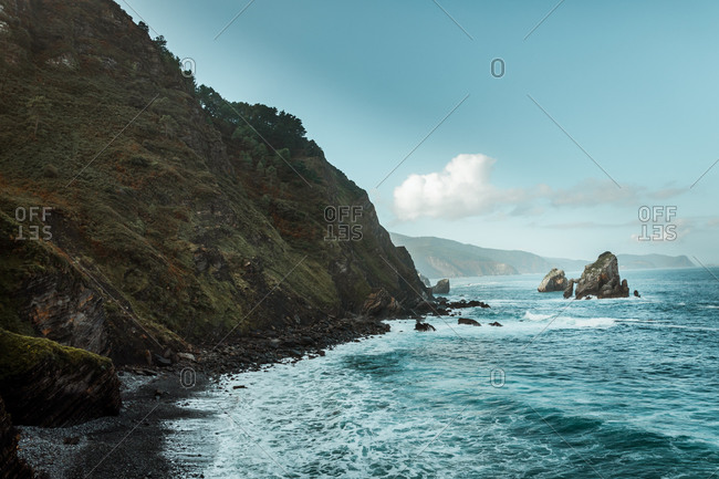 Scenery view of ocean with pure water and waves forming foam while touching hillside covered with plants and grass in daylight