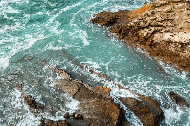 Top view of troubled turquoise sea with waves passing between natural rocky formations with shabby uneven surface