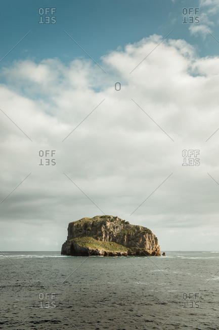 Picturesque view of rocky cliff with uneven surface washed by ocean