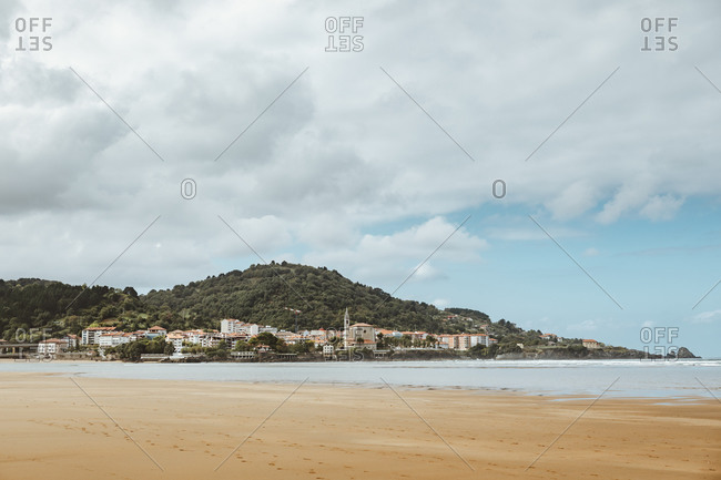 Calm ocean with sandy coast near green mountain with buildings under cloudy sky in afternoon