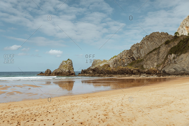 Magnificent view of tranquil ocean and sand beach with footprints near big rock in afternoon under blue sky with clouds