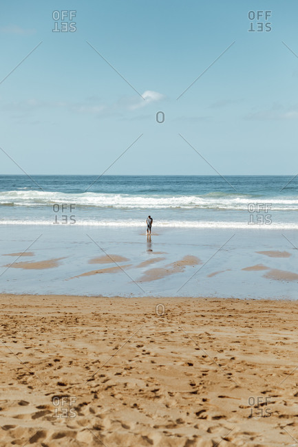 Back view of anonymous traveler standing on picturesque sea coast near sand with footprints under cloudy sky on sunny day