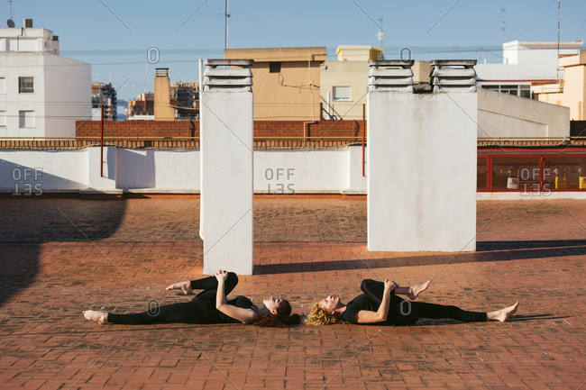 Women practicing supine yoga pose together