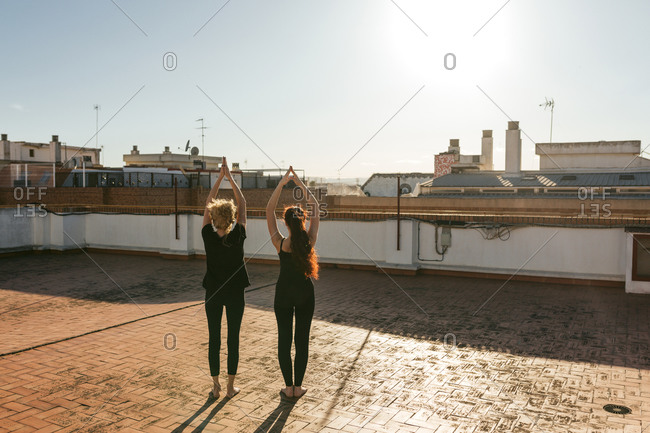 Full body back view of mature woman with young daughter in black sportswear standing in Upward Salute position with raised arms while doing Sun Salutation sequence during yoga practice on rooftop