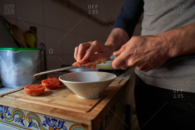 Stock photo of the detail of hands of a man grating tomato on top of a piece of wood in a kitchen