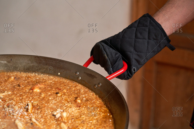 Stock photo of Hand with a black kitchen glove taking the handle of a rice paella