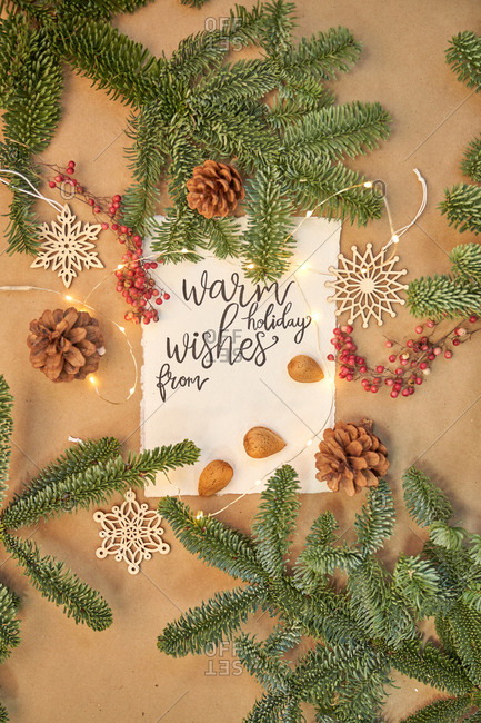 Christmas greeting written with a beautiful handmade letter with Christmas decorations and lights around.