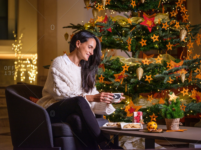 Woman drinking a cup of hot chocolate on the sofa of her house with a Christmas tree and Christmas decorations in the background.