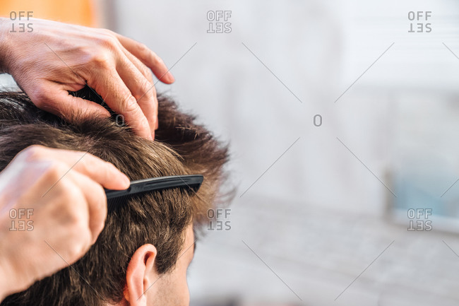Crop man brushing hair of young guy and doing hairstyle in bright bathroom