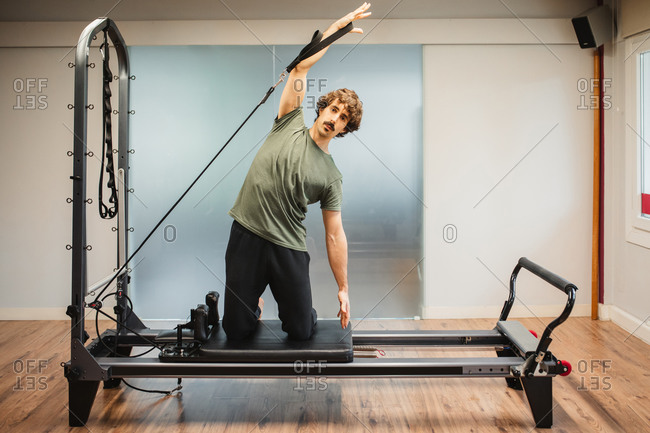 Sportsman in activewear using pilates machine and stretching arms with resistance bands