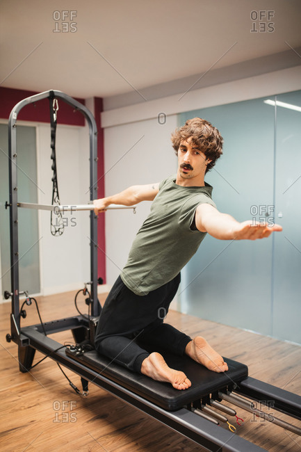 Athlete in sportswear doing exercises with pilates reformer during training in gym