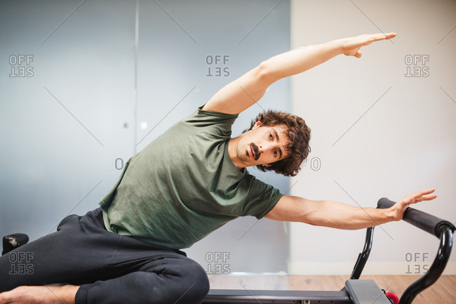 Focused male athlete in activewear sitting on pilates machine and doing side bends while looking at camera during training