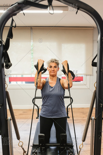 Determined female in sportswear pumping muscles with resistance bands while using pilates machine and looking at camera during workout