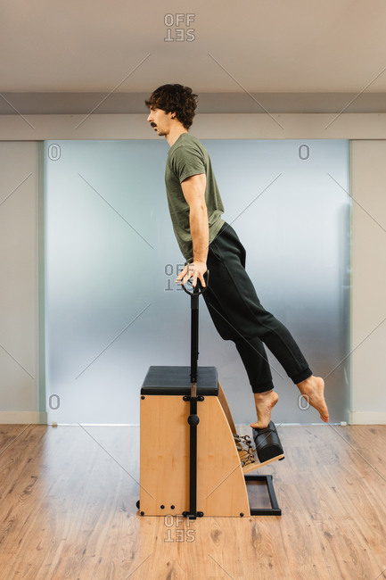 Side view of strong sportsman balancing on hands on pilates chair during workout in modern gym