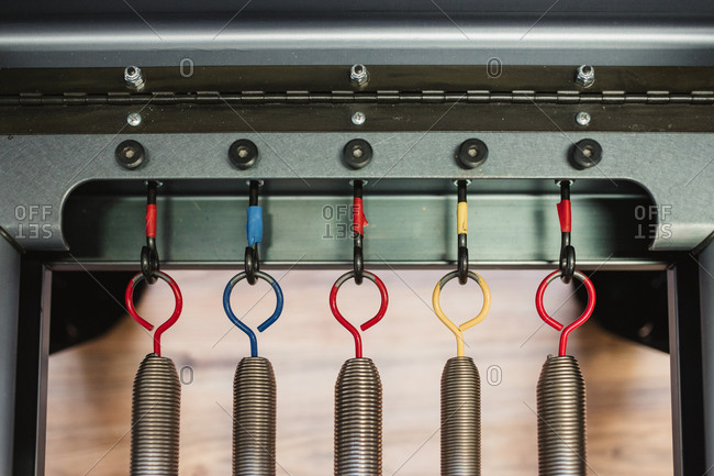 Top view of metal springs on hooks of modern pilates reformer placed in gym