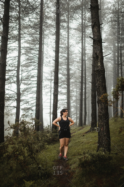 Fit woman walking along path in misty forest