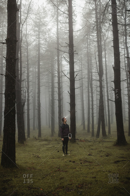 Fit sportsman in activewear and head torch standing in foggy forest