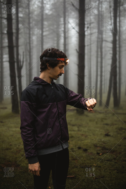 Fit sportsman in activewear and head torch standing in foggy forest and checking time on wristwatch during morning workout