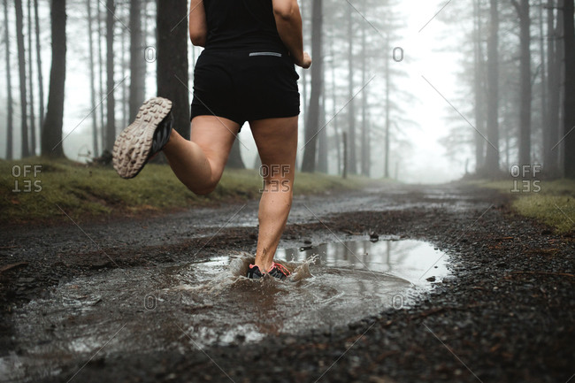 Back view of faceless female runner in activewear training in woods and running through dirty puddle in woods
