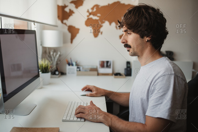 Side view of focused male freelancer sitting at table in creative workspace and typing on keyboard while working on online project
