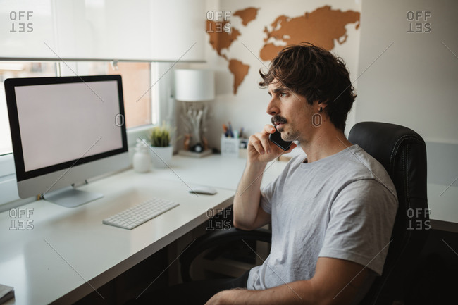 Side view of focused male freelancer sitting at table in creative workspace using mobile phone while working on online project