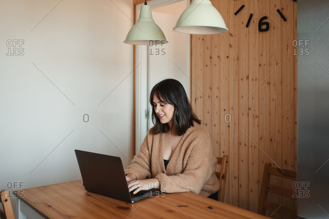 Smiling female freelancer in cozy sweater sitting at table in kitchen and working on project while using computer