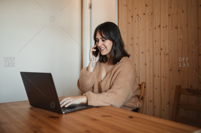 Side view of businesswoman sitting at table with laptop and speaking on smartphone during remote work