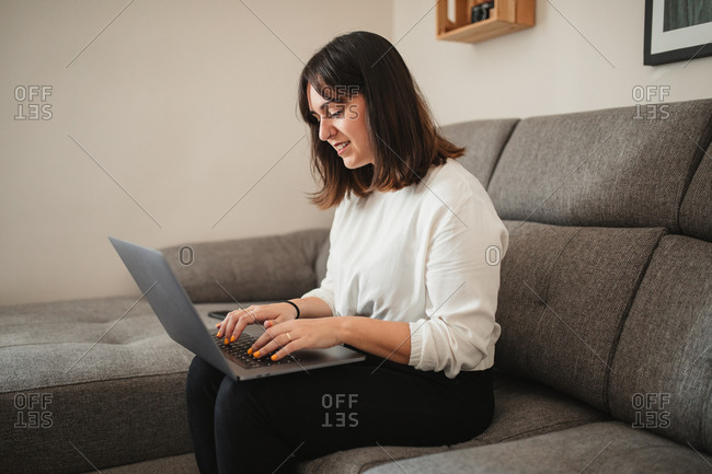 Confident female entrepreneur in casual clothes sitting on sofa in living room while browsing on computer during remote work