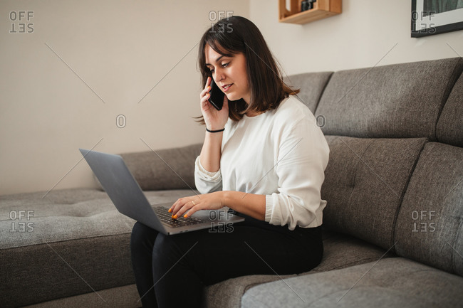 Confident female entrepreneur in casual clothes sitting on sofa in living room and discussing project on cellphone while browsing netbook during remote work