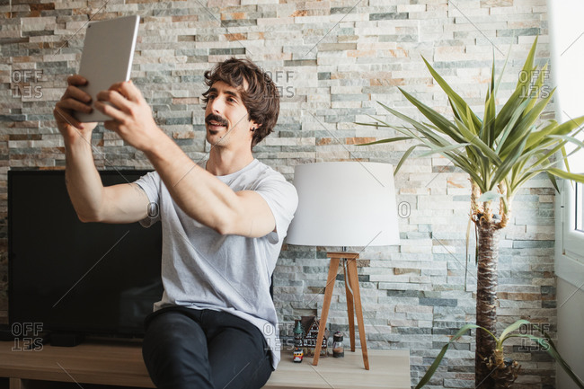 Relaxed male in casual wear sitting making video call on tablet while enjoying weekend at home