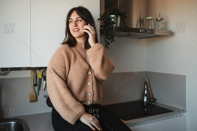 Delighted female in trendy sweater sitting in kitchen countertop and having a conversation on a mobile phone