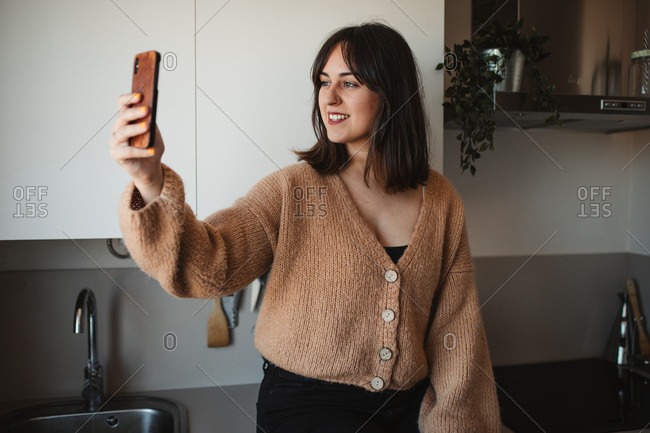 Delighted female in trendy sweater standing in kitchen and having conversation via video call