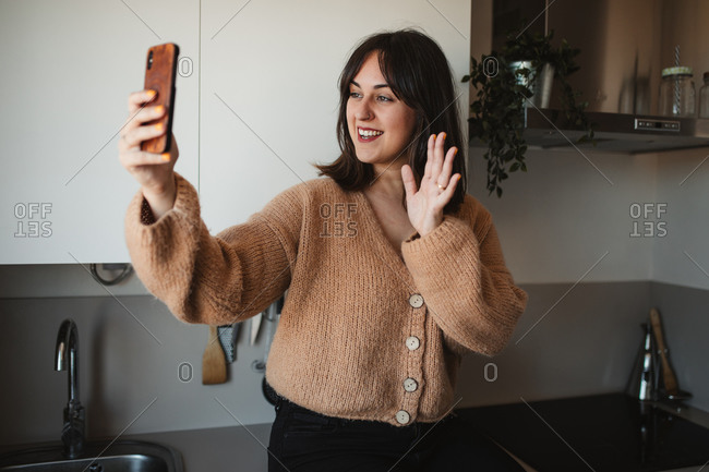 Delighted female in trendy sweater standing in kitchen and having conversation via video call while making greeting gesture