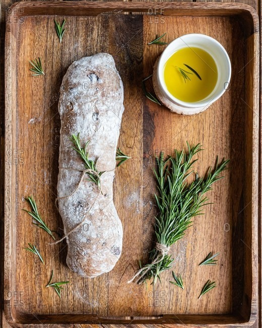 Top view of delicious Italian ciabatta bread served on wooden tray with pot of olive oil and fresh rosemary