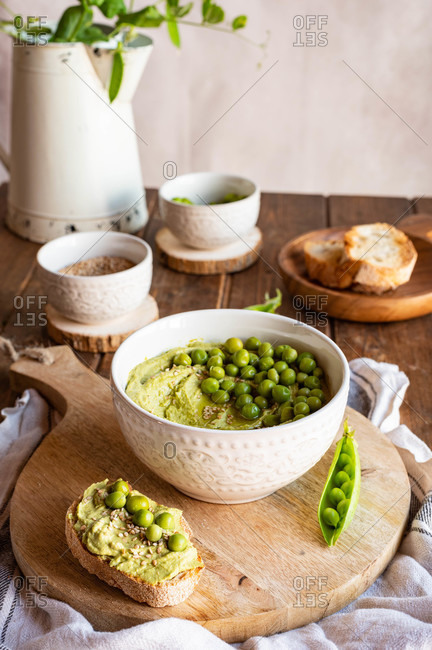 Composition with bowl with hummus made with green pea arranged on wooden table with ingredients for recipe and bread slices
