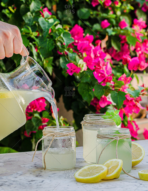 Crop anonymous person pouring fresh homemade lemonade from pitcher into glass jars placed on table in blooming summer garden