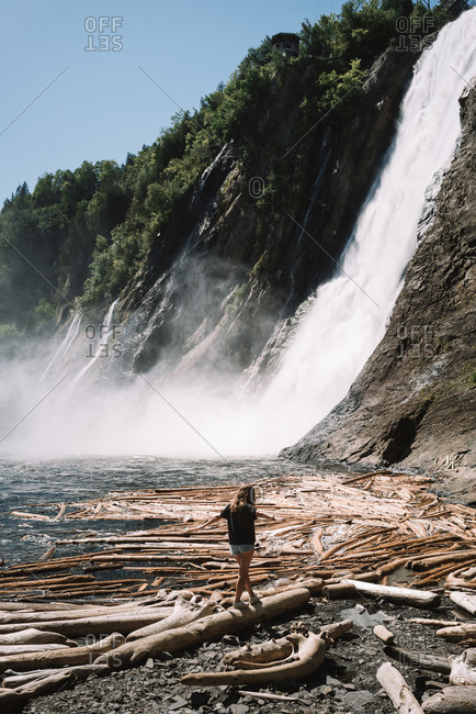 High angle back view of solitary girl walking along wet sand beach among snags against waterfall in sunny day