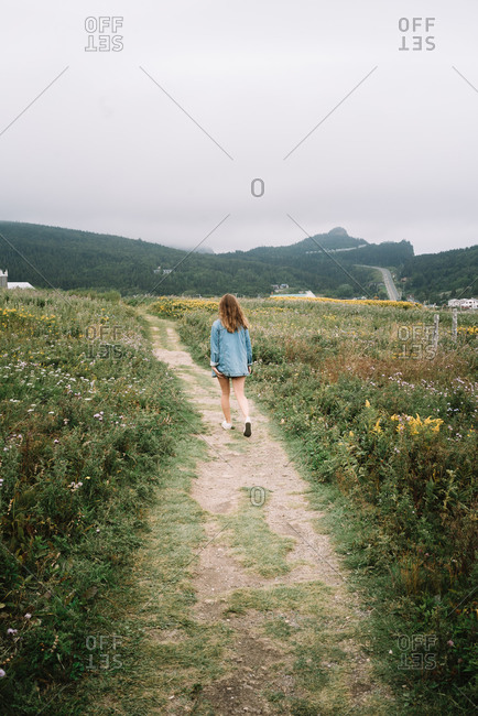 Unrecognizable female in summer wear walking along sandy pathway between meadows with flowers on overcast day