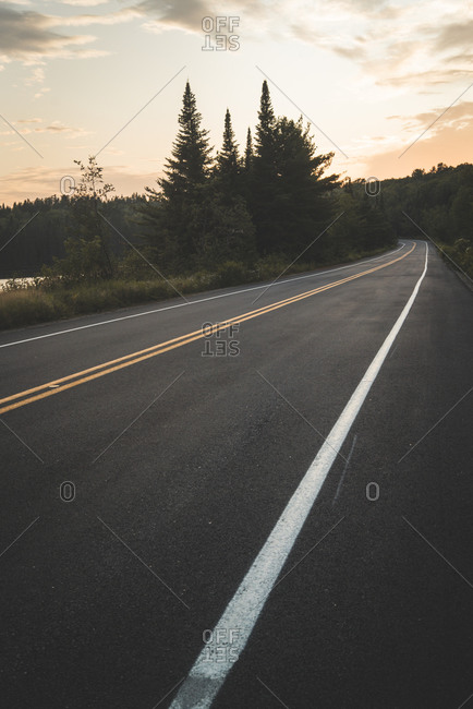 Asphalt road going near peaceful lake and green forest against cloudy sunset sky in La Mauricie National Park in Quebec, Canada