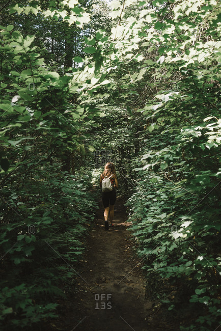 Woman with backpack walking in forest and enjoying weather in green forest of La Mauricie National Park in Quebec, Canada