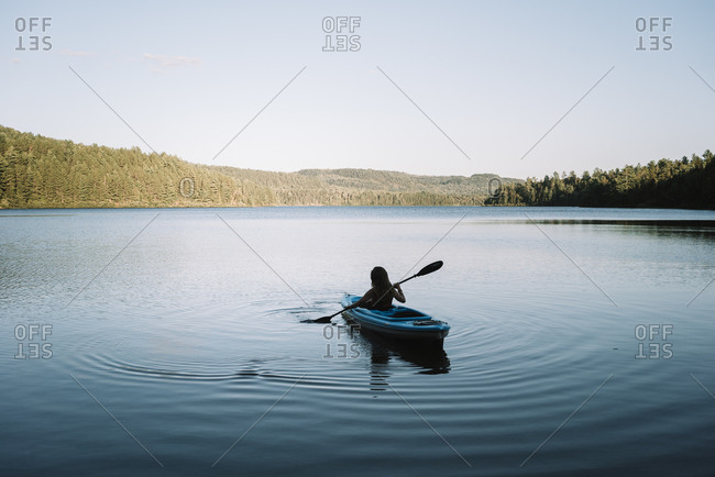 Silhouette of anonymous female traveler sitting on kayak and rowing during trip on calm river on cloudless day in La Mauricie National Park in Quebec, Canada