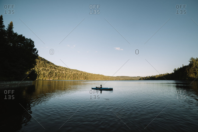 Silhouette of anonymous male traveler sitting on kayak and rowing during trip on calm river on cloudless day in La Mauricie National Park in Quebec, Canada