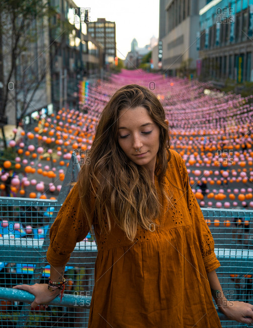 Calm brunette in dark orange dress standing on bridge with view of Montreal street decorated with multicolored garlands with eyes closed
