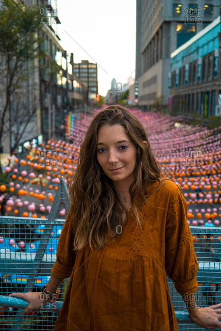 Calm brunette in dark orange dress standing on bridge with view of Montreal street decorated with multicolored garlands looking at camera