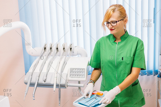 Adult friendly female dentist in green uniform and glasses getting instruments ready for patient visit in hospital office