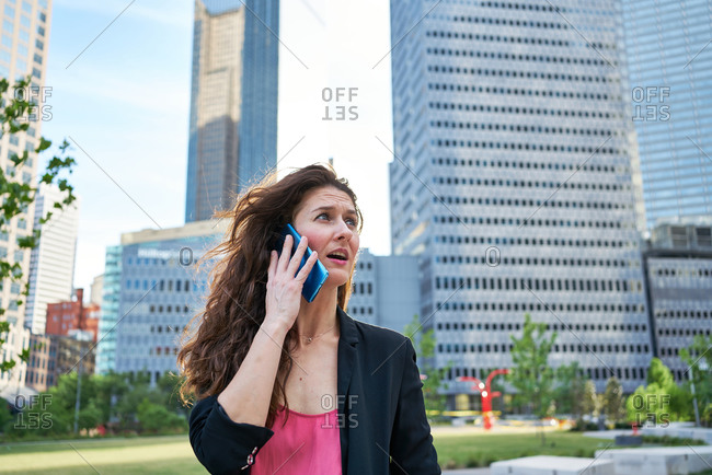 Content businesswoman in elegant jacket discussing work issues while speaking on cellphone and standing on blurred background of skyscrapers